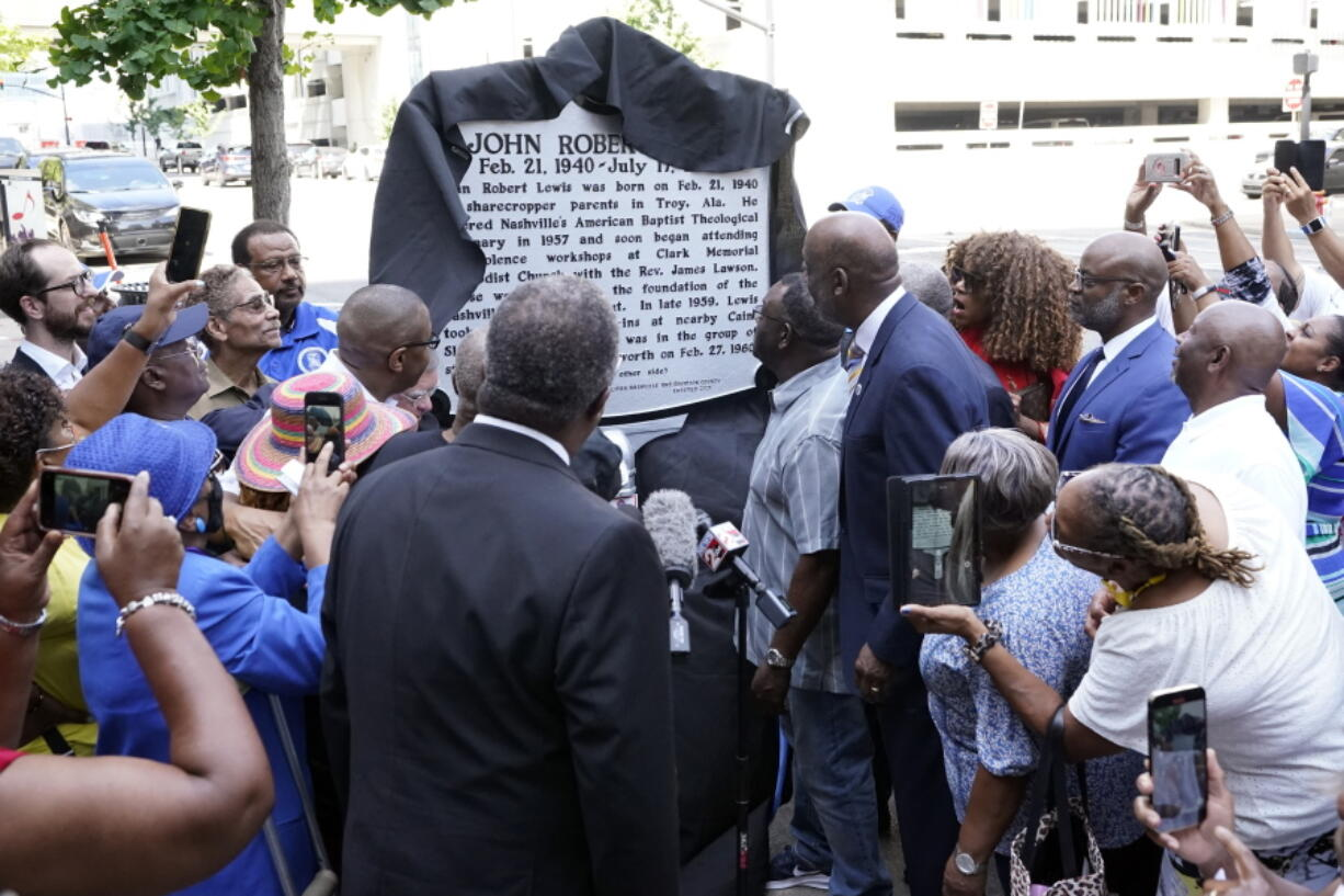 People watch as a new historical marker remembering former Rep. John Lewis is unveiled Friday, July 16, 2021, in Nashville, Tenn. Earlier this year, Nashville's Metro Council renamed a large portion of Fifth Avenue to Rep. John Lewis Way.