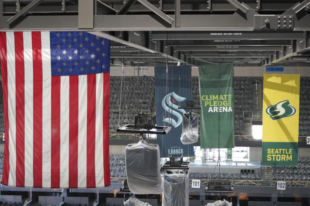 United States and team flags hang in the rafters of the Climate Pledge Arena during a media tour of the facility on Monday, July 12, 2021, in Seattle. The NHL expansion team Seattle Kraken will begin to fill out its roster with the expansion draft on Wednesday, July 21, 2021.  (AP Photo/Ted S.