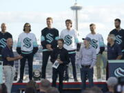 New Seattle Kraken NHL hockey players, back row from left, Mark Giordano, Brandon Tanev, Jamie Oleksiak, Hadyn Fluery, Jordan Eberle and Chris Dreidger stand on stage with Kraken owners David Wright, front left, Jerry Bruckheimer, front center, and Andy Jassy, front second from right, and Kraken general manager Ron Francis, front right, Wednesday, July 21, 2021, after being introduced during the Kraken's expansion draft event in Seattle. Jassy is also president and CEO of Amazon.com. (AP Photo/Ted S.