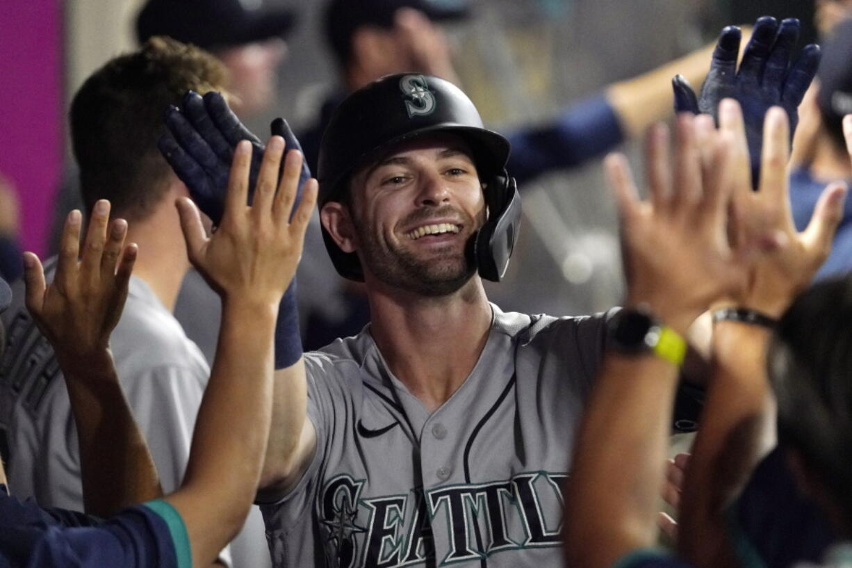 Seattle Mariners' Mitch Haniger is congratulated by teammates after hitting a two-run home run during the seventh inning of a baseball game against the Los Angeles Angels Friday, July 16, 2021, in Anaheim, Calif. (AP Photo/Mark J.