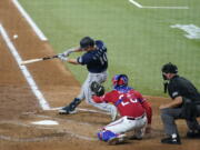 Seattle Mariners' Jarred Kelenic (10) connects for a three-run home run in front ot Texas Rangers' Jonah Heim and umpire Scott Barry during the third inning of a baseball game in Arlington, Texas, Friday, July 30, 2021.