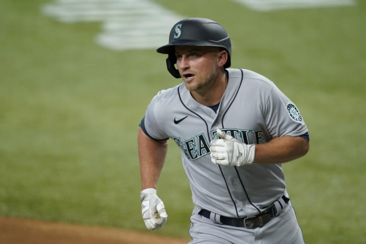 Seattle Mariners' Kyle Seager crosses the plate after hitting a two-run home run during the first inning of the team's baseball game against the Texas Rangers in Arlington, Texas, Saturday, July 31, 2021.