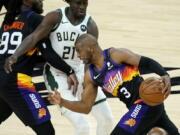 Phoenix Suns guard Chris Paul (3) drives pst Milwaukee Bucks guard Jrue Holiday (21) during the second half of Game 1 of basketball's NBA Finals, Tuesday, July 6, 2021, in Phoenix. (AP Photo/Matt York) (Ross D.