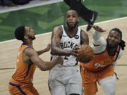 Milwaukee Bucks forward Khris Middleton, center, drives to the basket between Phoenix Suns guard Cameron Payne, left, and forward Jae Crowder, right, during the second half of Game 4 of basketball's NBA Finals Wednesday, July 14, 2021, in Milwaukee.