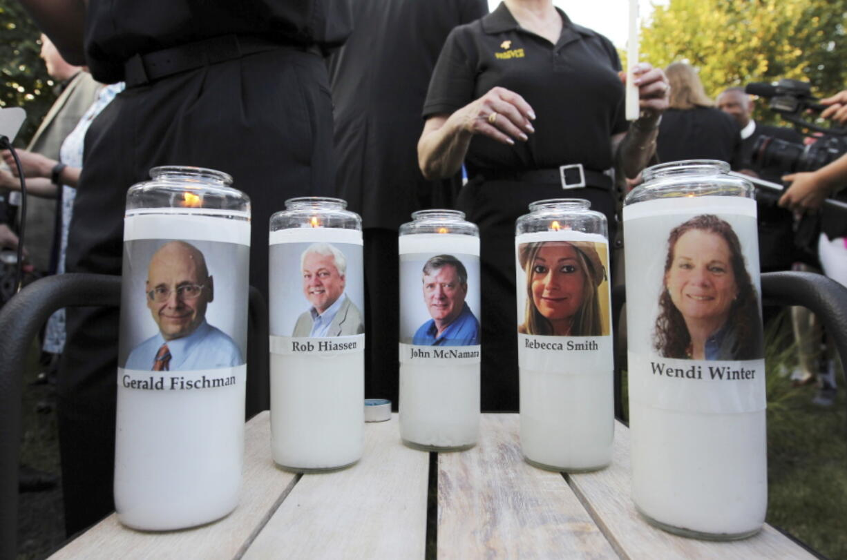 FILE - In this June 29, 2018, file photo, pictures of five employees of the Capital Gazette newspaper adorn candles during a vigil across the street from where they were slain in the newsroom in Annapolis, Md. A jury was selected on Friday, June 25, 2021, for the second phase of a trial for a man who killed the five people at the newspaper to decide whether he is criminally responsible due to his mental health. Jarrod Ramos pleaded guilty in 2019 to all 23 counts against him in the attack at the Capital Gazette nearly three years ago, but he has pleaded that he is not criminally responsible due to mental illness.