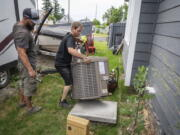 Carl Rocha, left, and Patrick Plummer, with Bills Heating & A/C Install air conditioning and a new furnace at a home on East Wabash Street, Wednesday, June 23, 2021, in Spokane, Wash. With temperatures forecast to hit over 100 degrees by Sunday, a rush of customers are keeping local A/C installers busy.