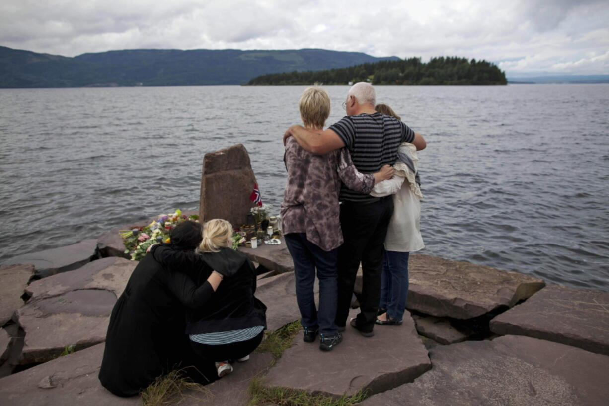 FILE - In this Monday, July 25, 2011 file photo, relatives of a victim gather to observe a minute's silence on a campsite jetty on the Norwegian mainland, across the water from Utoya island, seen in the background, where people have been placing floral tributes in memory of those killed in the shooting massacre on the island.  At 3.25 p.m. on July 22, 2021, a ray of sun should have illuminated the first of 77 bronze columns on a lick of land opposite Utoya island outside Oslo. Over the next 3 hours and 8 minutes, it would have brushed each column in turn, commemorating every person killed by right-wing terrorist Anders Breivik. But on the ten-year anniversary of the terror, the memorial remains a construction site.