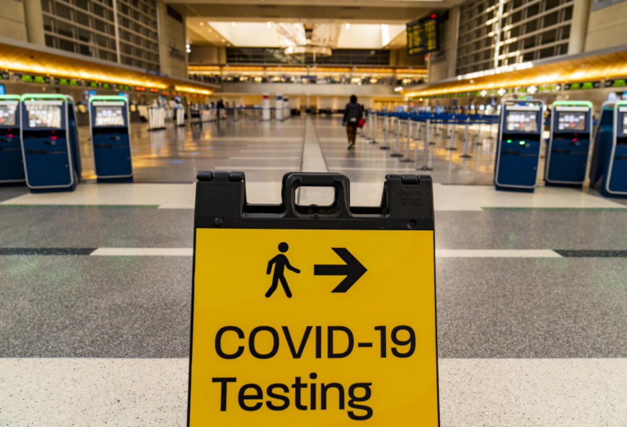 """FILE - In this Nov. 25, 2020 file photo, a COVID-19 testing sign is posted at the empty Tom Bradley International Terminal at Los Angeles International Airport.  On Friday, July 30, 2021 The Associated Press reported on stories circulating online incorrectly claiming a table shows a list of planned COVID-19 variants and when they will be """"released"""" to the public."""
