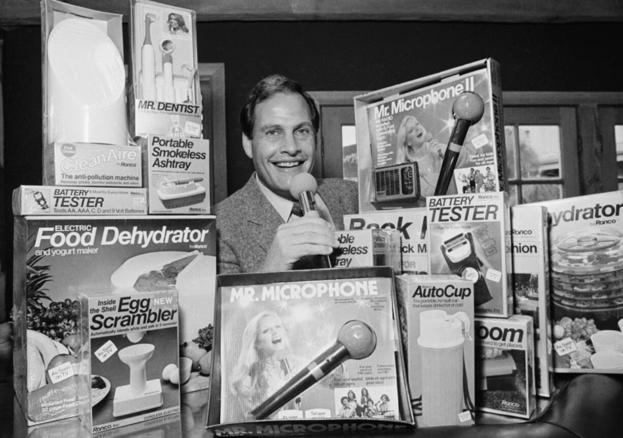 FILE - In this Wednesday, Dec. 8, 1982 file photo, Ron Popeil, the man behind those late-night, rapid-fire television commercials that sell everything from the Mr. Microphone to the Pocket Fisherman to the classic Veg-a-Matic, sits surrounded by his wares in his office in Beverly Hills, Calif.  Ron Popeil, the quintessential TV pitchman and inventor known to generations of viewers for hawking products including the Veg-O-Matic, the Chop-O-Matic, Mr. Microphone and the Showtime Rotisserie and BBQ, died Wednesday, July 28, 2021 his family said.
