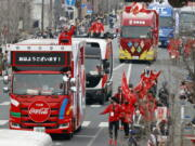 FILE - In this March 28, 2021, file photo, Olympic sponsors' vehicles parade ahead of torch relay in Ashikaga, Tochigi prefecture, north of Tokyo. The Olympic corporate sponsorship program has been a key part of the Olympic experience since it began in 1985. But all that magic from the Olympic sponsorship is being undermined because of the virus.