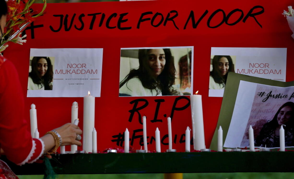 A women's rights activist places a candle beside a poster with the pictures of Noor Mukadam, who was recently beheaded, during a candle light vigil to pay tribute to Noor and other domestic violence victims, in Islamabad, Pakistan, Sunday, July 25, 2021. The killing of Mukadam in an upscale neighborhood of Pakistan's capital has shone a spotlight on the relentless violence against women in the country. Rights activists say such gender-based assaults are on the rise as Pakistan barrels toward greater religious extremism.