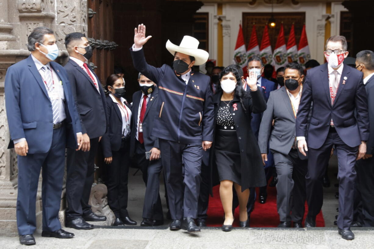 Peru's President-elect Pedro Castillo and his wife Lilia Paredes wave as they leave the Foreign Ministry to go to Congress for his swearing-in ceremony on his Inauguration Day in Lima, Peru, Wednesday, July 28, 2021.