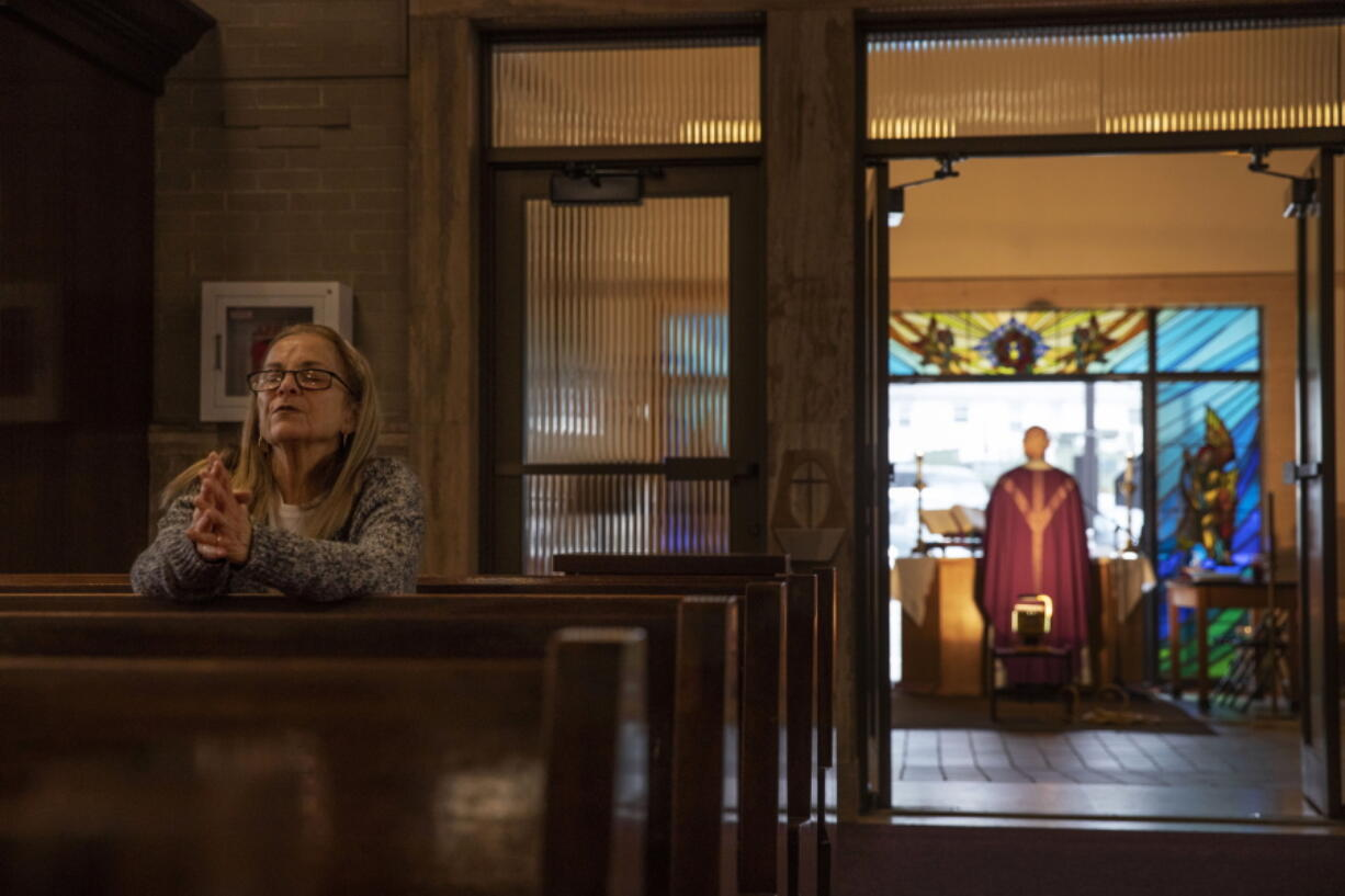 FILE - Fran DiBiasio sits alone in Our Lady of Grace Catholic Church as Rev. Peter Gower celebrates Mass from the front door as worshippers listen over the radio from their cars in the parking lot, Sunday, March 29, 2020, in Johnston, R.I. For the first time in nearly two decades, only half of U.S. households donated to a charity, according to a study released Tuesday, July 27, 2021.  Experts say many factors are contributing to the decline. The percentage of Americans who give to religious causes has decreased in tandem with attendance at worship services as the number of Americans not affiliated with any religion grows.