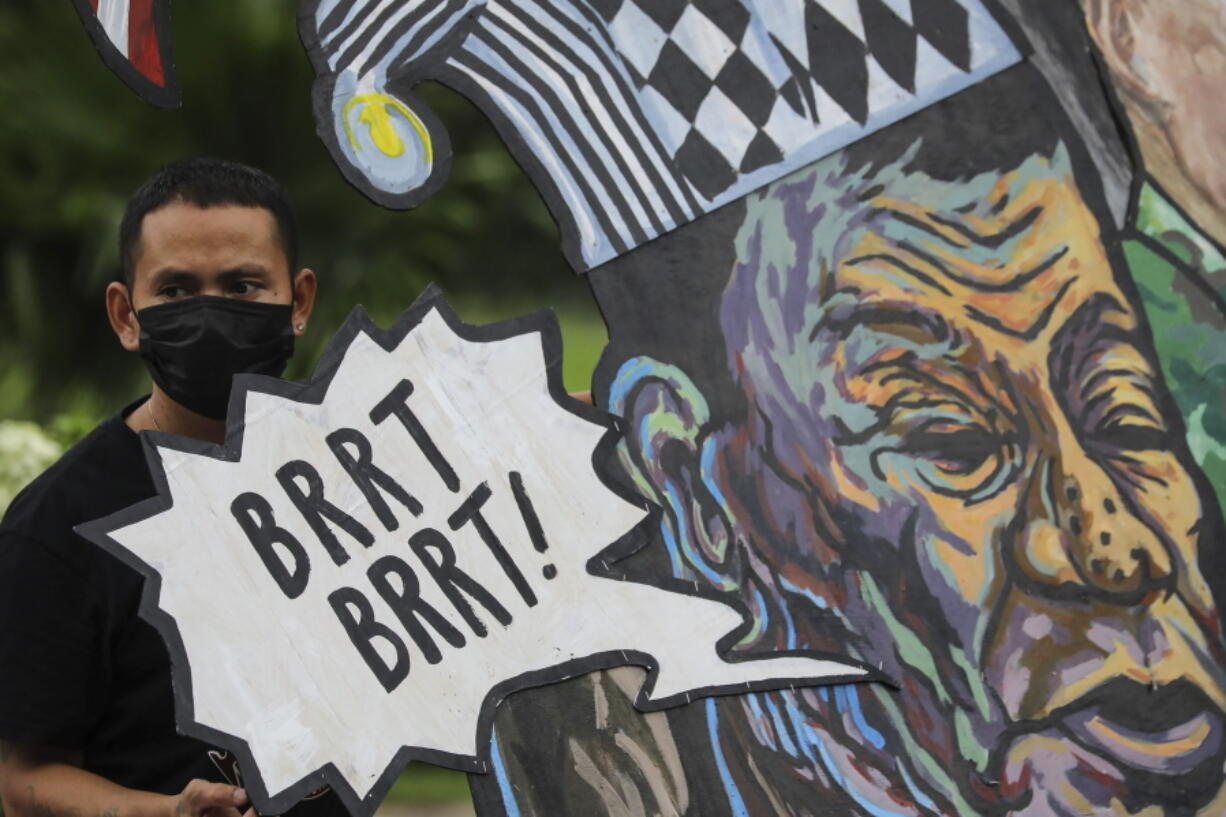 A protester stands beside a caricature of Philippine President Rodrigo Duterte before marching towards the House of Representatives where he is set to deliver his final State of the Nation Address in Quezon city, Philippines on Monday, July 26, 2021. Duterte is winding down his six-year term amid a raging pandemic and a battered economy.