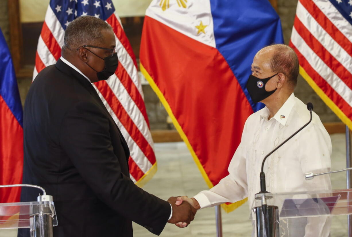 United States Defense Secretary Lloyd Austin, left, and Philippines Defense Secretary Delfin Lorenzana shake hands after a bilateral meeting at Camp Aguinaldo military camp in Quezon City, Metro Manila, Philippines Friday, July 30, 2021. Austin is visiting Manila to hold talks with Philippine officials to boost defense ties and possibly discuss the The Visiting Forces Agreement between the US and Philippines.