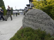 """Cadets LeAnne Cone, left, of the Vancouver Police Dept., and Kevin Burton-Crow, right, of the Thurston Co. Sheriff's Dept., walk past a rock at the Washington state Criminal Justice Training Commission engraved with """"WSCJTC Values Professionalism, Accountability Integrity,"""" on the way to a training exercise Wednesday, July 14, 2021, in Burien, Wash. Washington state is embarking on a massive experiment in police reform and accountability following the racial justice protests that erupted after George Floyd's murder last year, with nearly a dozen new laws that took effect Sunday, July 25, but law enforcement officials remain uncertain about what they require in how officers might respond -- or not respond -- to certain situations, including active crime scenes and mental health crises. (AP Photo/Ted S."""