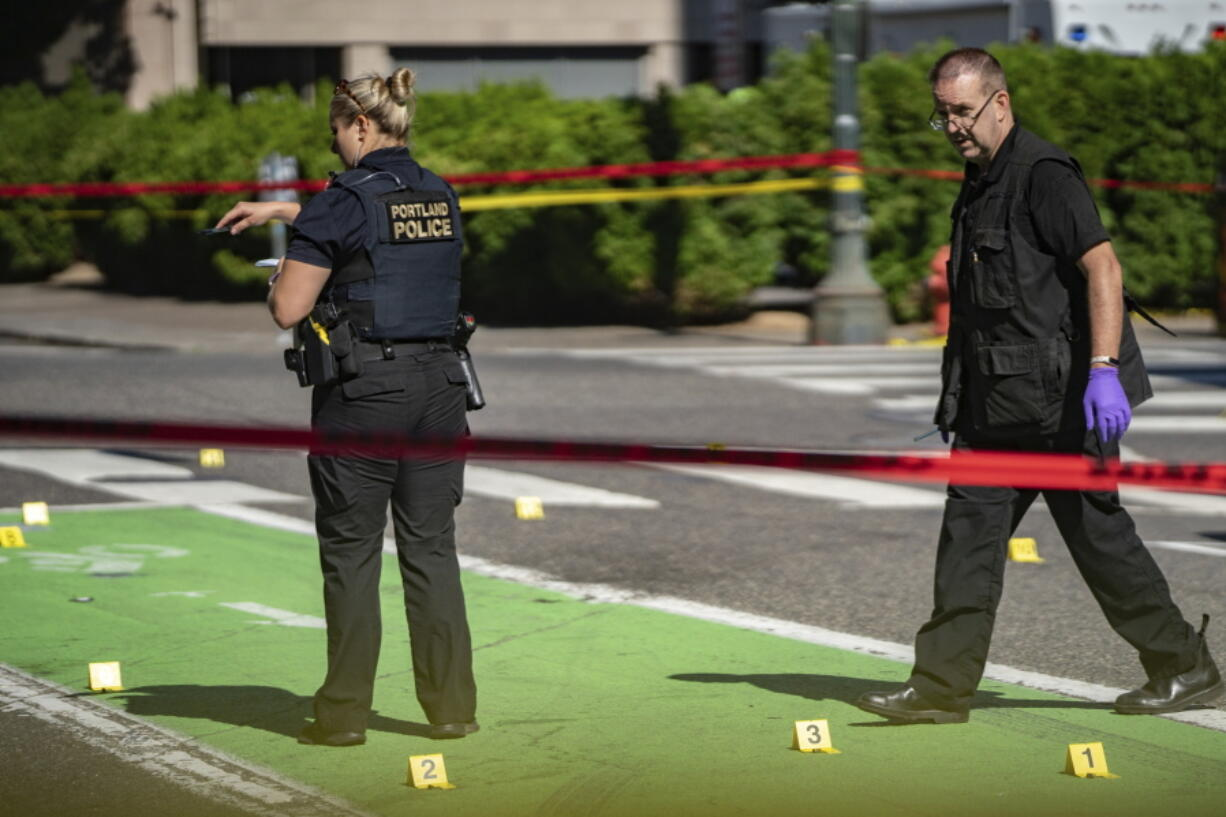 Police investigate an overnight shooting Saturday, July 17, 2021 in Portland, Ore. Police said one person died and at least six people were injured in an early morning shooting Saturday in Portland, Oregon.