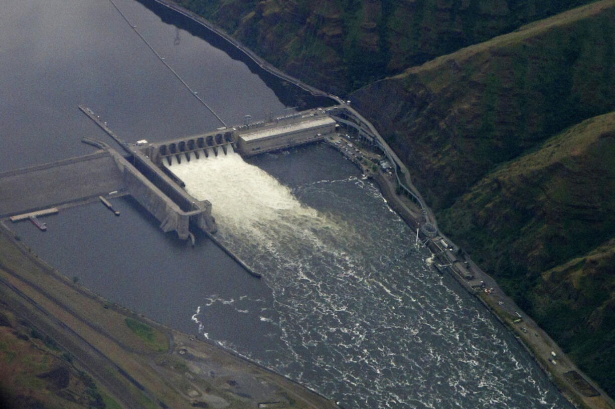 FILE - In this May 15, 2019 file photo, the Lower Granite Dam on the Snake River is seen from the air near Colfax, Wash. The record-shattering heat wave in the Pacific Northwest has prompted fishing and conservation groups to ask a federal court to order more spill from dams on the lower Snake and Columbia Rivers next spring to aid the migration of endangered salmon and steelhead runs. (AP Photo/Ted S.