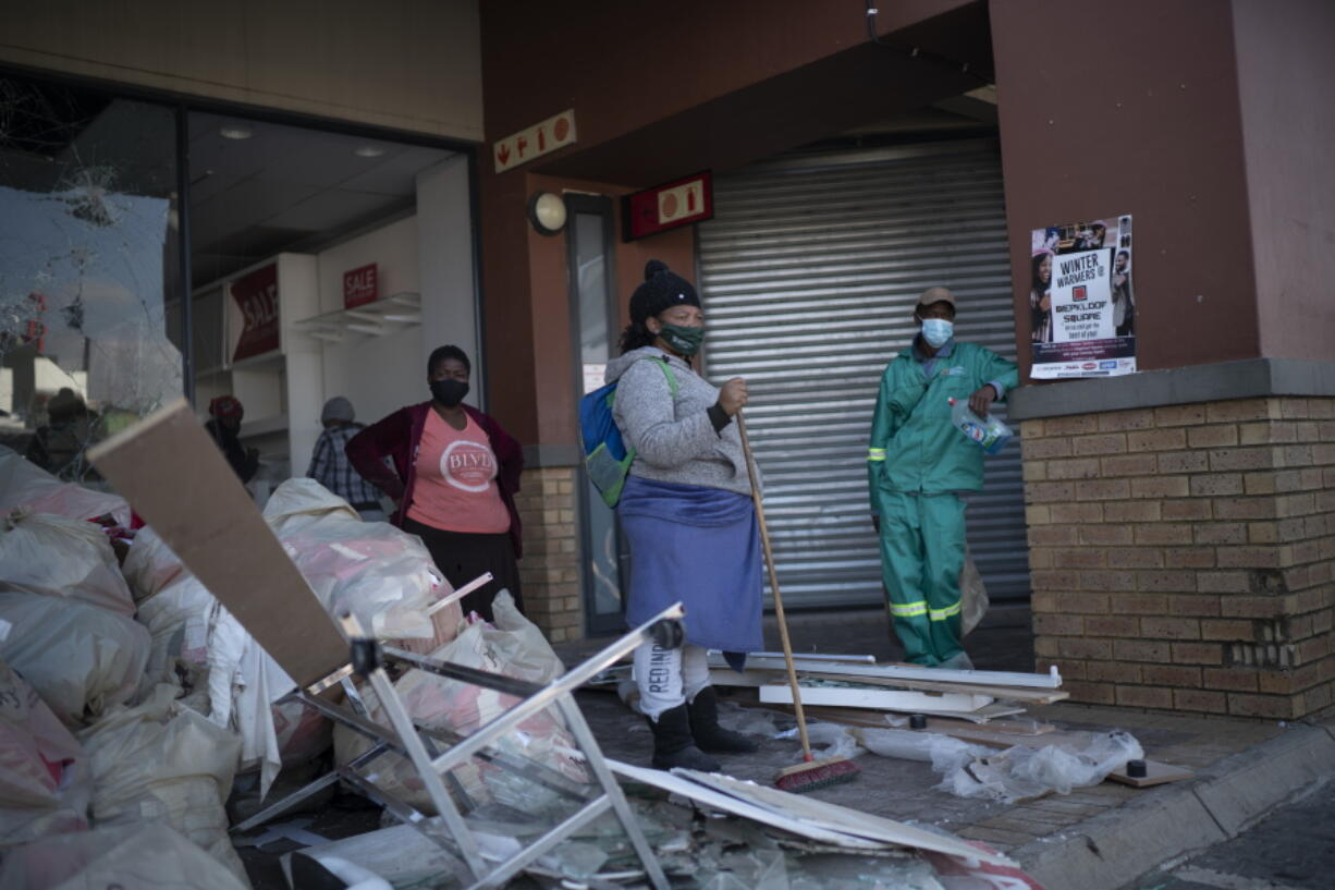 Volunteers participate in the cleaning efforts at Soweto's Diepkloof mall outside Johannesburg, South Africa, Thursday July 15, 2021. A massive cleaning effort has started following days of violence in Gauteng and KwaZulu-Natal provinces.