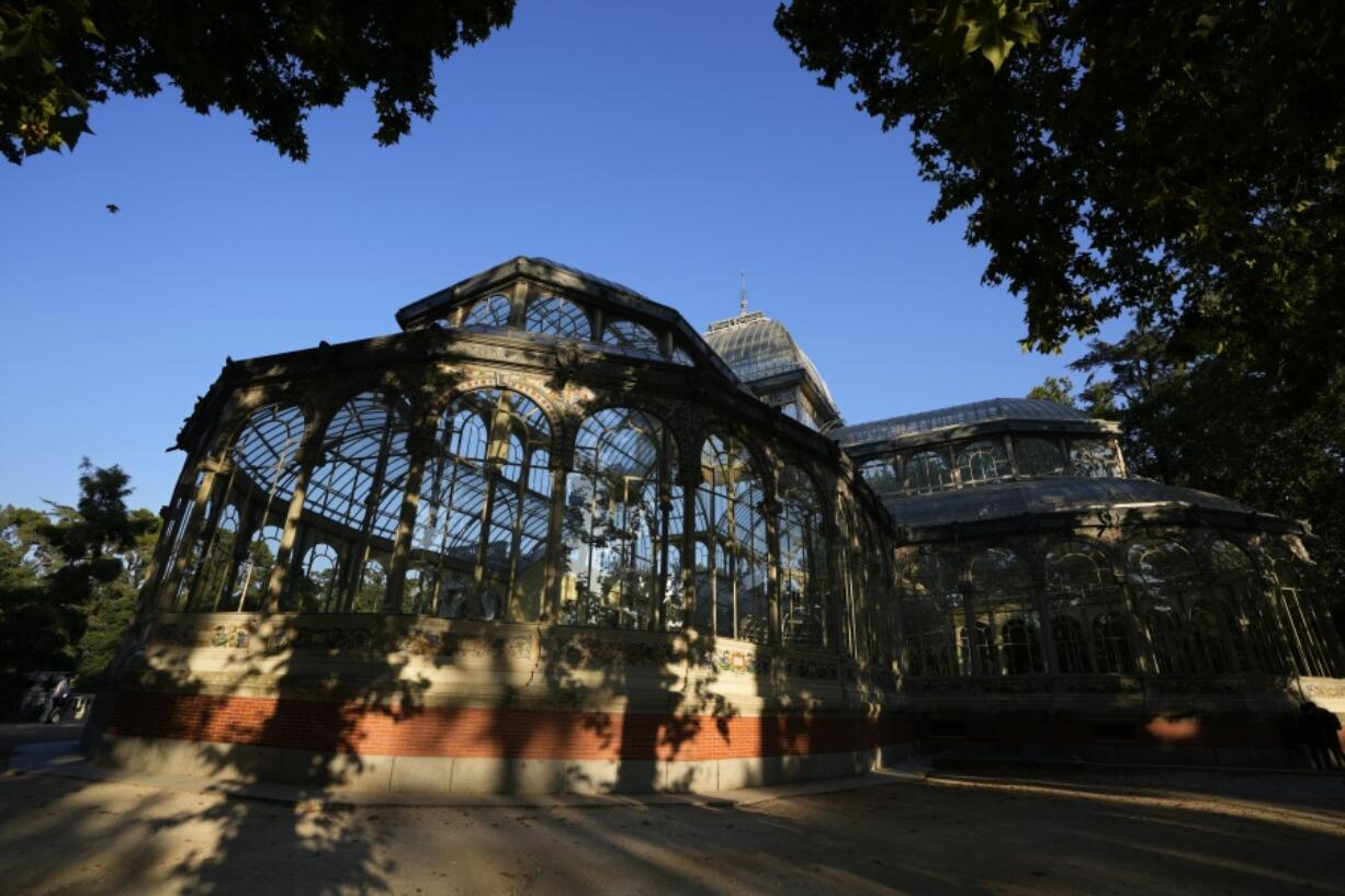 The Glass Palace stands shaded by trees in the Retiro park in Madrid, Spain, Thursday, July 22, 2021. Madrid's tree-lined Paseo del Prado boulevard and the adjoining Retiro park have been added to UNESCO's World Heritage list. The UNESCO World Heritage Committee backed the candidacy that highlighted the green area's introduction of nature into Spain's capital.