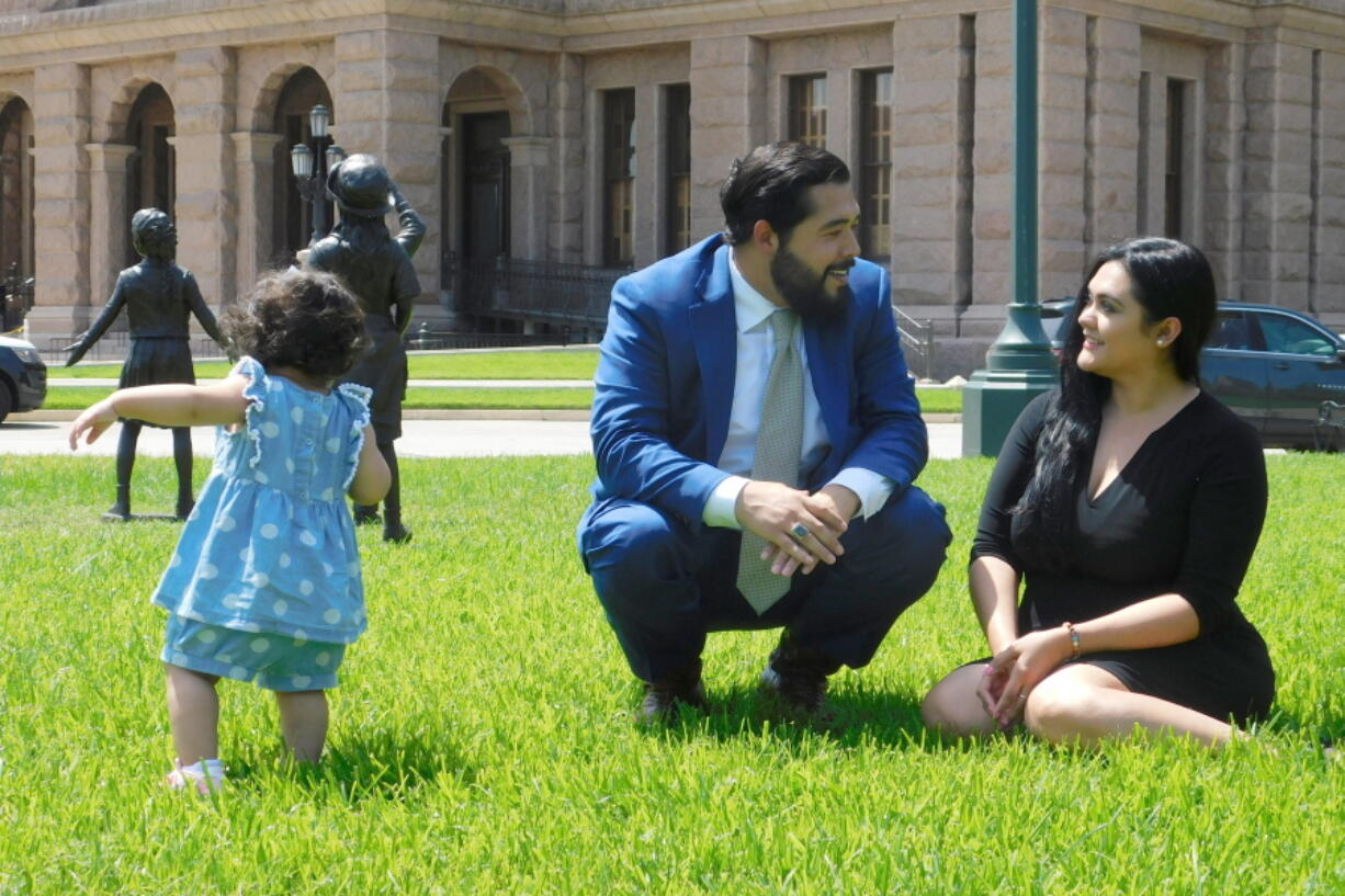 Donovon Rodriguez, chief of staff for Texas state Rep. Ray Lopez, walks around the Texas capitol with his wife, Jenny Tavarez, and daughter, Evelyn Belle Rodriguez, for whom he is the sole provider, Monday, July 26, 2021 in Austin, Texas. Rodriguez could lose his job by Sept. 1, if legislative budget funding is not restored. Texas.