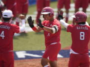 Japan's Minori Naito, center, celebrates with her teammates after hitting a two run home run during the softball game between Japan and Australia at the 2020 Summer Olympics, Wednesday, July 21, 2021, in Fukushima, Japan. (AP Photo/Jae C.