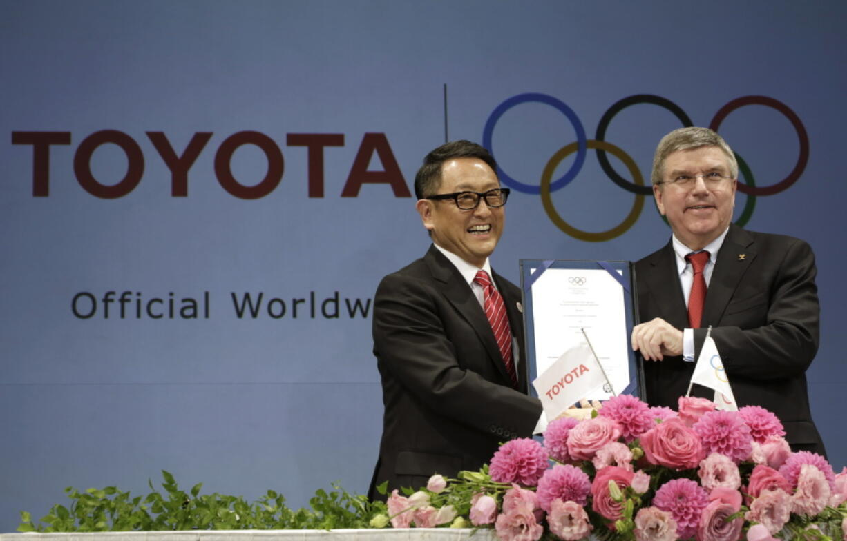 FILE - In this March 13, 2015 file photo, Toyota President and CEO Akio Toyoda, left, and IOC President Thomas Bach pose with a signed document during a press conference in Tokyo as Toyota signed on as a worldwide Olympic sponsor in a landmark deal, becoming the first car company to join the IOC's top-tier marketing program. Toyota won't be airing any Olympic-themed advertisements on Japanese TV during the Tokyo Games despite being one of the IOC's top corporate sponsors.