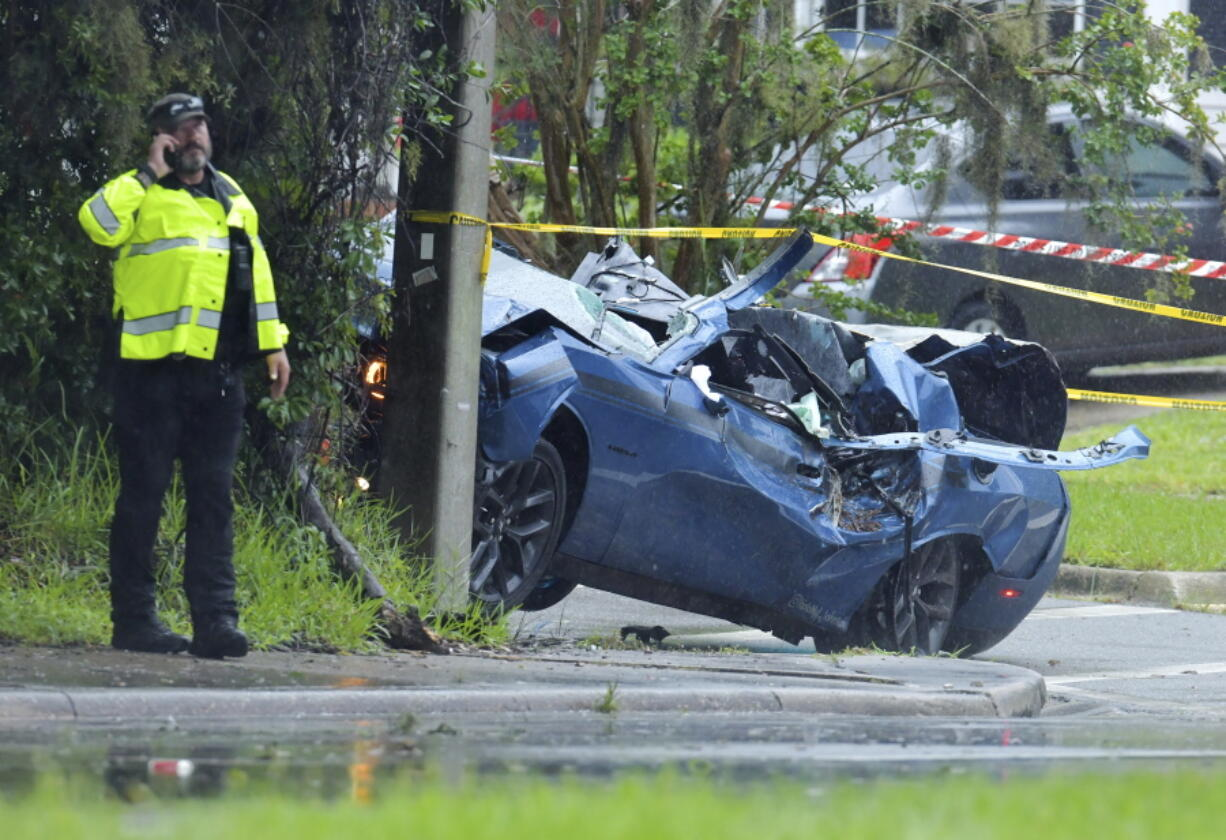 Law enforcement investigators in the scene of a fatal car crash on Roosevelt Blvd. in the Ortega neighborhood of Jacksonville, Fla. during the strong winds from Tropical Storm Elsa, Wednesday, July 7, 2021.