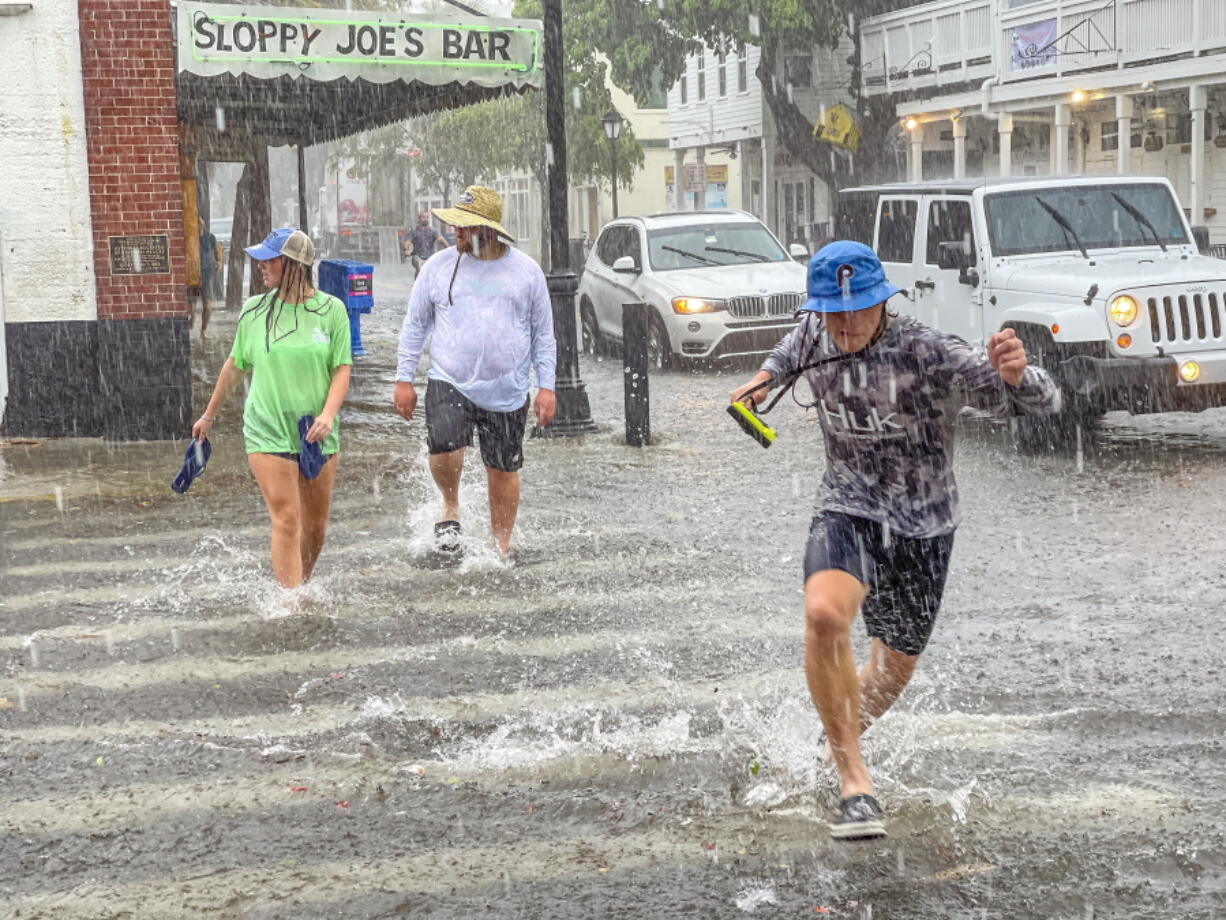 Pedestrians dash across the intersection of Greene and Duval streets as heavy winds and rain associated with Tropical Storm Elsa passes Key West, Fla., on Tuesday, July 6, 2021. The weather was getting worse in southern Florida on Tuesday morning as Tropical Storm Elsa began lashing the Florida Keys, complicating the search for survivors in the condo collapse and prompting a hurricane watch for the peninsula's upper Gulf Coast.