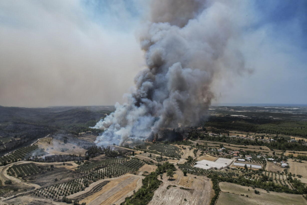 An aerial photo shows wildfires in Kacarlar village near the Mediterranean coastal town of Manavgat, Antalya, Turkey, Saturday, July 31, 2021. The death toll from wildfires raging in Turkey's Mediterranean towns rose to six Saturday after two forest workers were killed, the country's health minister said. Fires across Turkey since Wednesday burned down forests, encroaching on villages and tourist destinations and forcing people to evacuate.