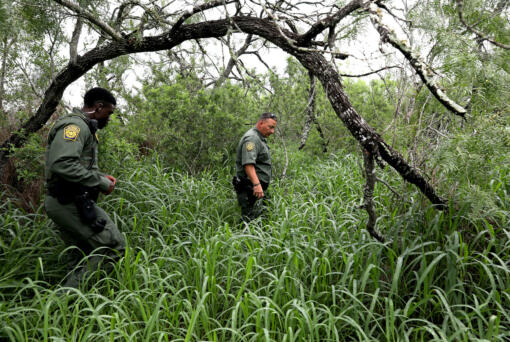 U.S. Customs and Border Protection Agents Ebenezar Oyenola, left, and Jaime Cavazos search for missing Honduran migrant Yoel Nieto Valladares, 25, on a south Texas ranch on June 3, 2021.