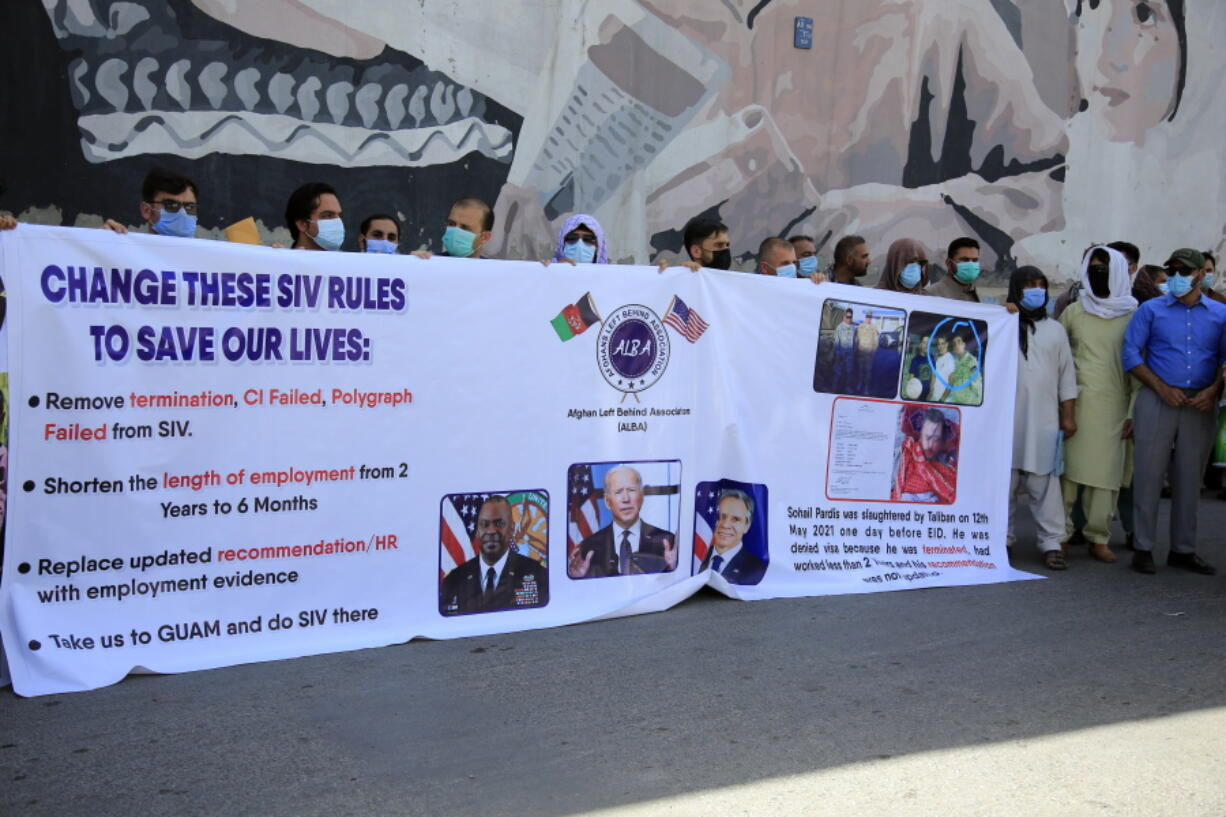 In this June 25, 2021 photo, former Afghan interpreters hold placards during a demonstrations against the US government, in front of the US Embassy in Kabul, Afghanistan.  The Biden administration says it will evacuate about 2,500 Afghans who worked for the U.S. government and their families to a military base in Virginia pending approval of their visas. The administration notified Congress on Monday that the Afghans will be housed at the Fort Lee Army base south of Richmond starting next week.