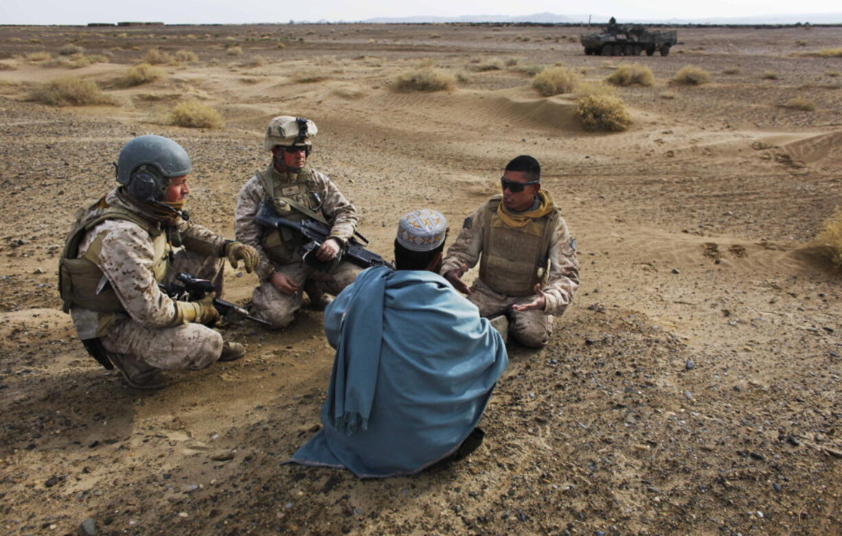 FILE - In this Friday, Dec. 11, 2009, file photo, United States Marine Sgt. Isaac Tate, left, and Cpl. Aleksander Aleksandrov, center, interview a local Afghan man with the help of a translator from the 2nd MEB, 4th Light Armored Reconnaissance Battalion on a patrol in the volatile Helmand province of southern Afghanistan. More than 200 Afghans were due to land Friday in the United States in the first of several planned evacuation flights for former translators and others as the U.S. ends its nearly 20-year war in Afghanistan.