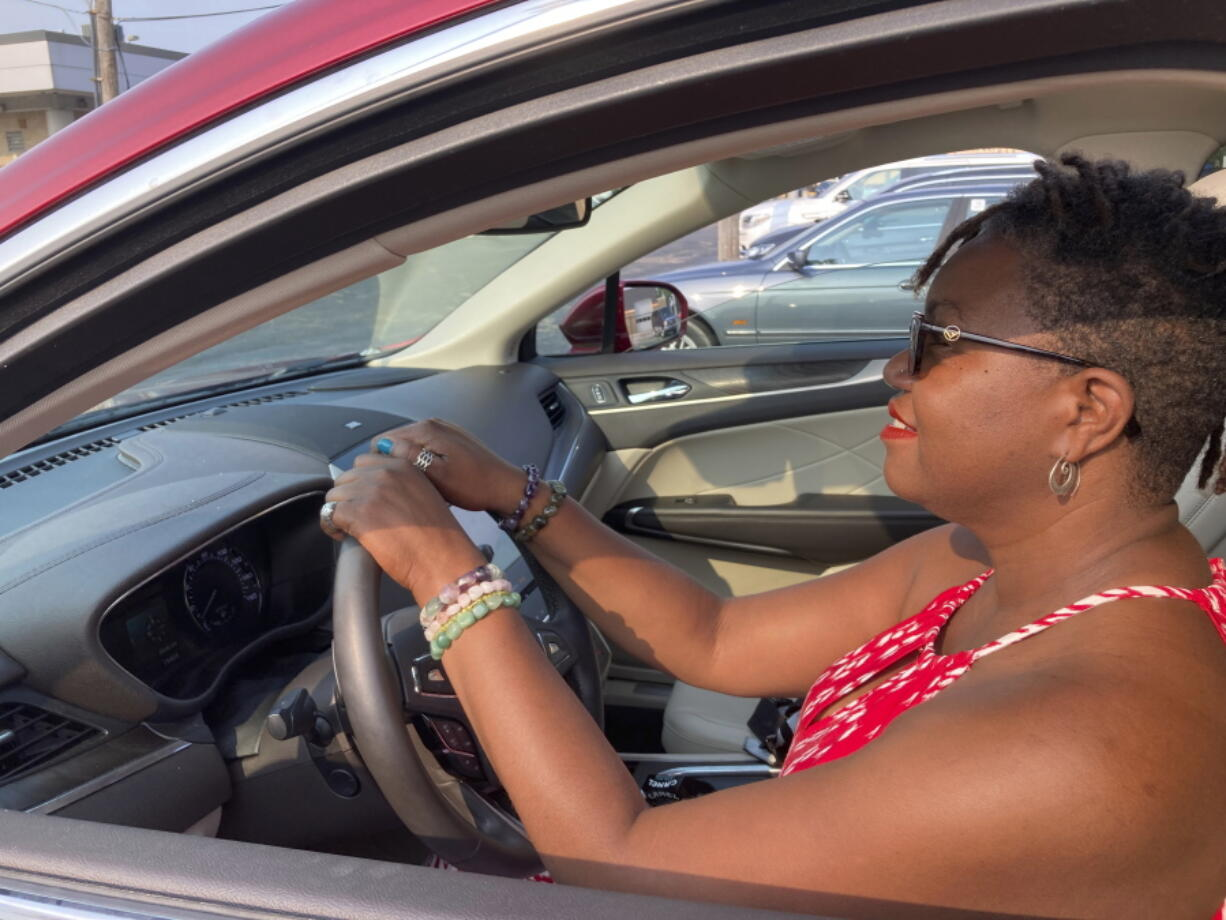 Jessica Pitts sits behind the wheel of a 2019 Lincoln MKC on the lot of Jack Demmer Lincoln in Dearborn, Mich., on Monday, July 19, 2021. Pitts bought the used car at the dealership.