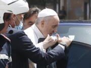 FILE - In this July 14, 2021 file photo, Pope Francis stops to greet police that escorted him as he arrives at the Vatican after leaving the hospital 10 days after undergoing planned surgery to remove half his colon. The Vatican on Wednesday, July 21, 2021, released a grueling travel itinerary for Pope Francis' first post-surgery foreign trip, scheduling around-the-clock encounters and hop-scotching, in-country flights for his Sept. 12-15 visit to Hungary and Slovakia.