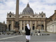FILE - In this Sunday, March 21, 2021 filer, a nun stands in St. Peter's Square at the Vatican. Vatican prosecutors have alleged a jaw-dropping series of scandals in launching the biggest criminal trial in the Vatican's modern history, which opens Tuesday in a modified courtroom in the Vatican Museums. The once-powerful cardinal and nine other people are accused of bleeding the Holy See of tens of millions of dollars in donations through bad investments, deals with shady money managers and apparent favors to friends and family.