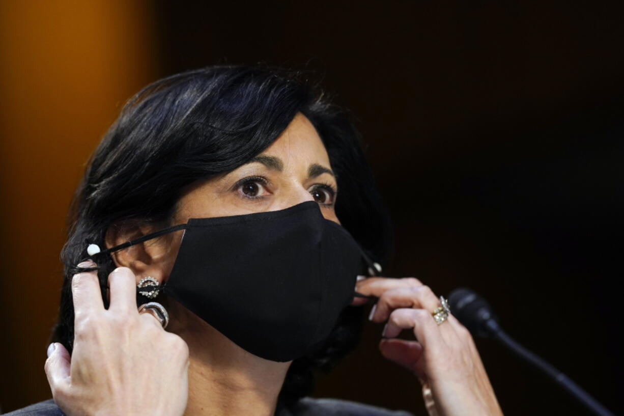 """FILE - Dr. Rochelle Walensky, director of the Centers for Disease Control and Prevention, adjusts her face mask during a Senate Health, Education, Labor and Pensions Committee hearing on the federal coronavirus response on Capitol Hill in Washington, in this Thursday, March 18, 2021, file photo. Walensky says new mask-wearing guidance, coupled with higher rates of vaccination against COVID-19, could halt the current escalation of infections in """"a couple of weeks."""" The director of the Centers for Disease Control and Prevention told """"CBS This Morning"""" she hopes more stringent mask-wearing guidelines and other measures won't be necessary as the country heads into the fall."""