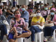 Residents wait to receives shots of the AstraZeneca COVID-19 vaccine at the Central Vaccination Center in Bangkok, Thailand, Thursday, July 15, 2021. As many Asian countries battle against a new surge of coronavirus infections, for many their first, the slow-flow of vaccine doses from around the world is finally picking up speed, giving hope that low inoculation rates can increase rapidly and help blunt the effect of the rapidly-spreading delta variant.