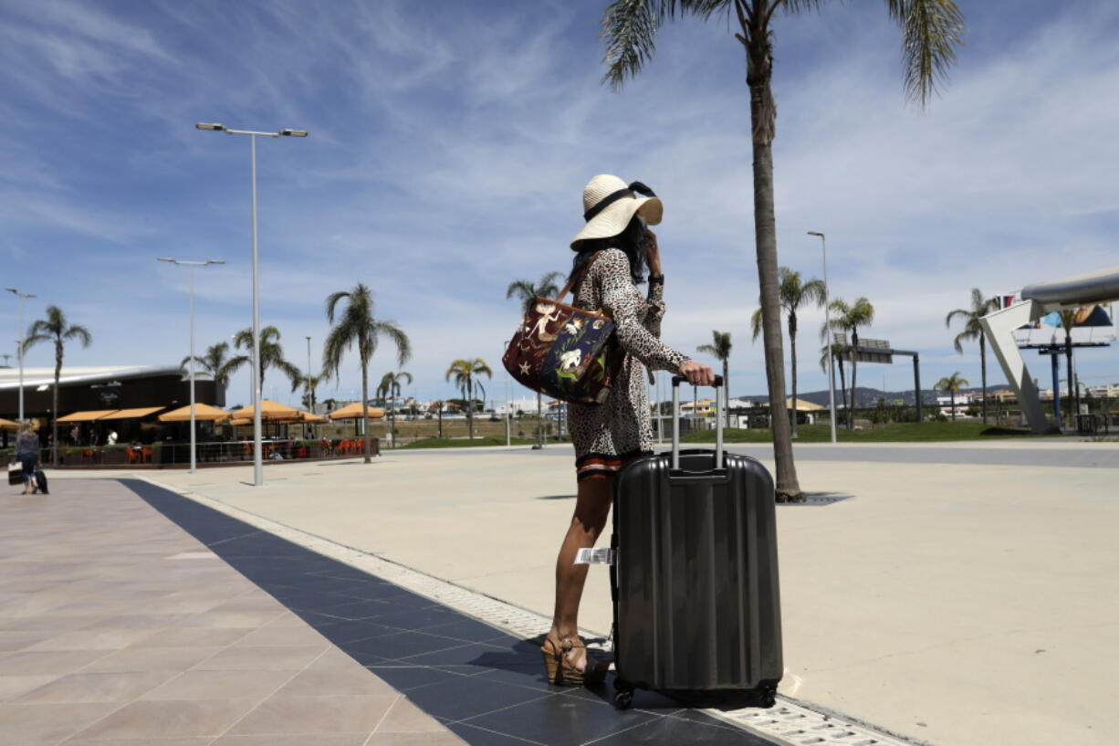 FILE - In this Monday, May 17, 2021 file photo, a passenger of a flight arriving at Faro leaves the airport, outside Faro, in Portugal's southern Algarve region. For Europe's battered tourism industry, fresh virus outbreaks and chaos and confusion over travel rules are contributing to another cruel summer.