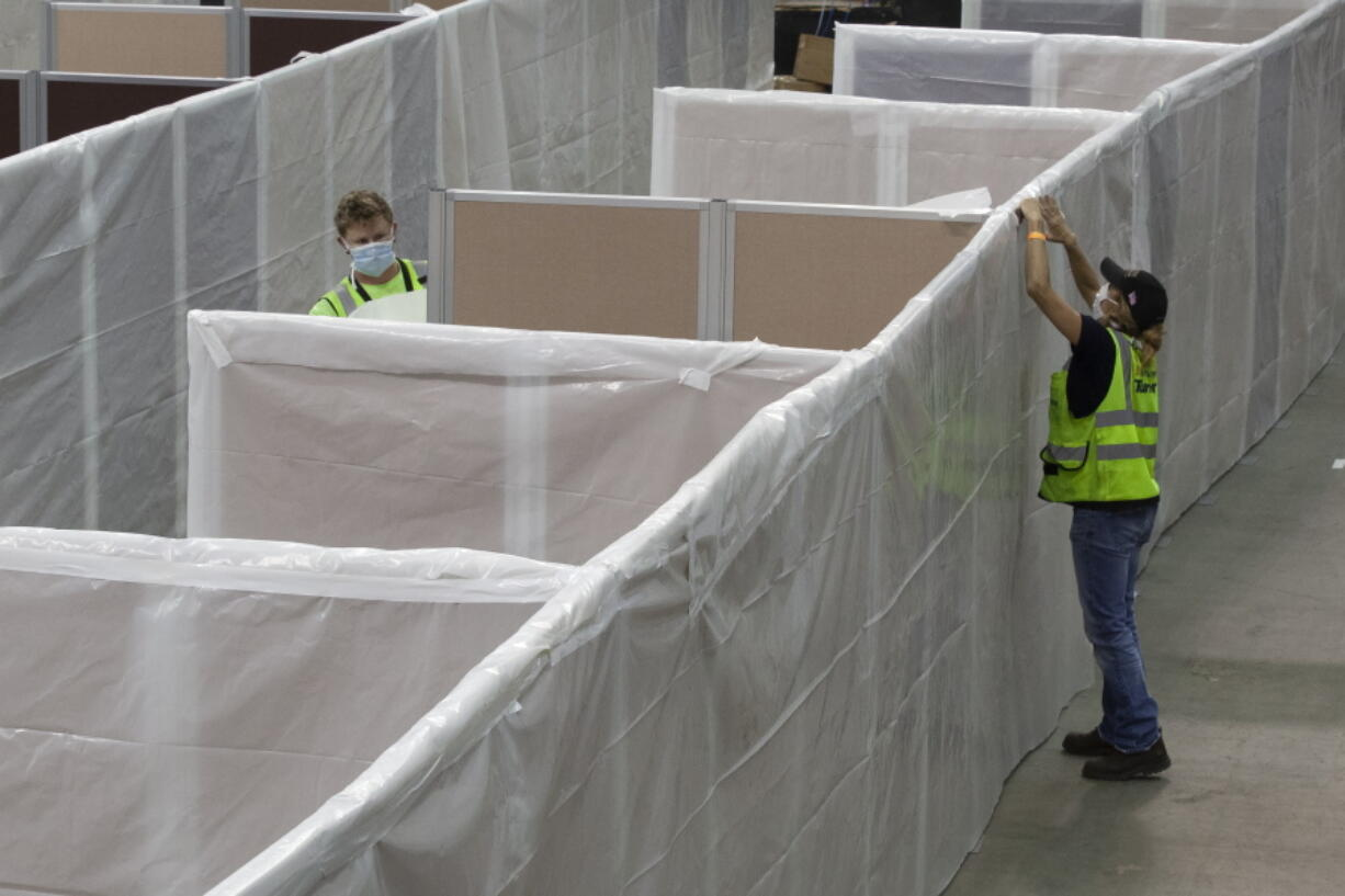FILE -- In this April 18, 2020 file photo sheeting is placed on partitions installed between beds as work is performed to turn the Sleep Train Arena into a 400 bed emergency field hospital to help deal with the coronavirus , in Sacramento, Calif.  California spent nearly $200 million to set up, operate and staff alternate care sites that ultimately provided little help when the state's worst coronavirus surge spiraled out of control last winter, forcing exhausted hospital workers to treat patients in tents and cafeterias.