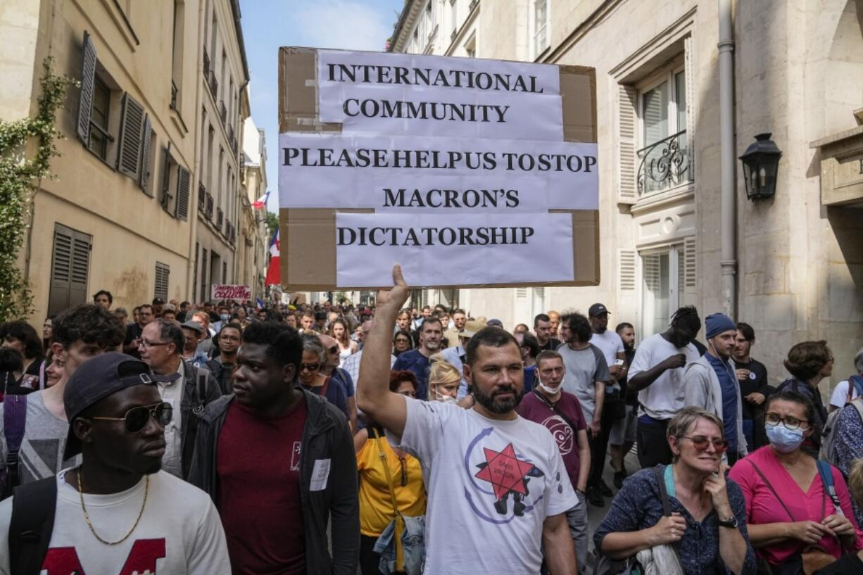 Anti-vaccine protester holds a placard during a rally in Paris, Saturday, July 17, 2021. Tens of thousands of people protested across France on Saturday against the government's latest measures to curb rising COVID-19 infections and drive up vaccinations in the country.