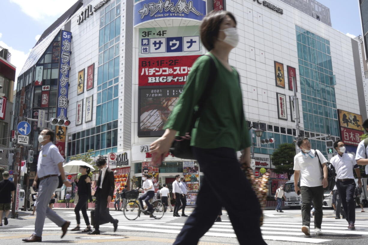 People walk across a crossing near Shimbashi Station in Tokyo Thursday, July 29, 2021, a day after the record-high coronavirus cases were found in the Olympics host city.
