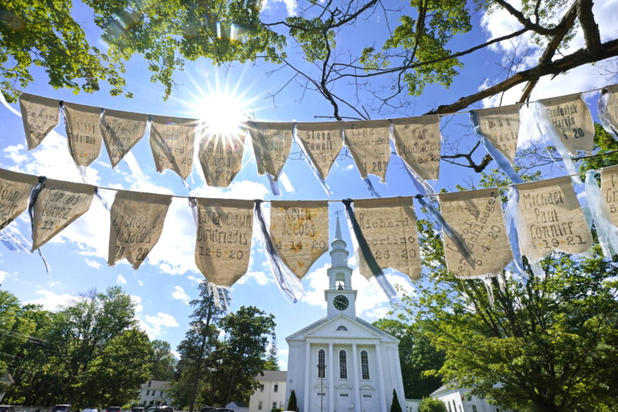 Flags with names of people who died from COVID-19 are displayed outside the First Congressional Church last month in Holliston, Mass. The flags are part of the COVID Art and Remembrance project spearheaded by Jaclyn Winer, whose father, Keith Jacobs, died in April 2020 from the coronavirus.