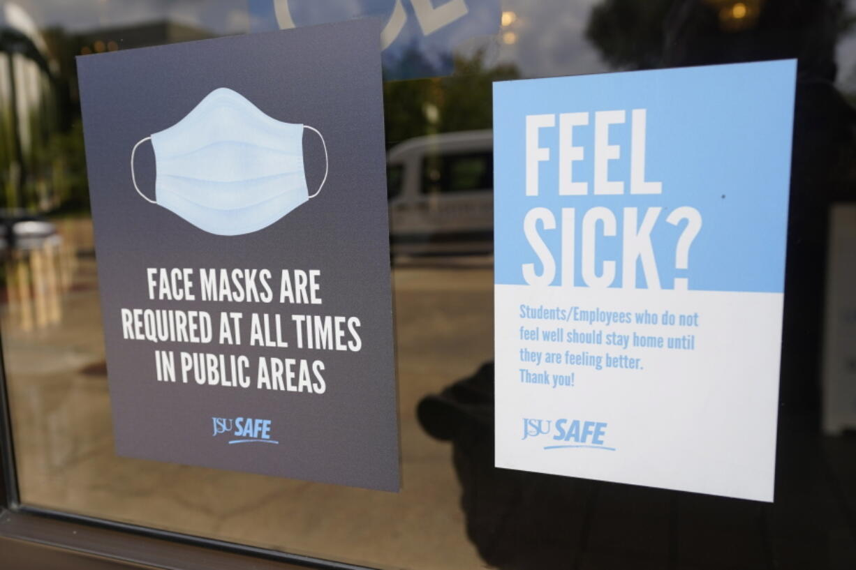 Face mask requirements are posted at the various entrances at the Rose E. McCoy Auditorium where COVID-19 vaccinations are being offered on the Jackson State University campus in Jackson, Miss., Tuesday, July 27, 2021. The university has similar signage posted throughout the campus. The Centers for Disease Control and Prevention announced new recommendations that vaccinated people return to wearing masks indoors in parts of the U.S. where the coronavirus is surging and also recommended indoor masks for all teachers, staff, students and visitors to schools, regardless of vaccination status. (AP Photo/Rogelio V.