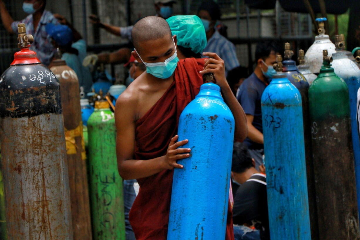 FILE - In this July 28, 2021, file photo, Buddhist monk wearing a face mask holds an oxygen tank for refill outside the Naing oxygen factory at the South Dagon industrial zone in Yangon, Myanmar. Supplies of medical oxygen are running low, and the government has put restrictions on its private sale in many places, saying it is trying to prevent hoarding.