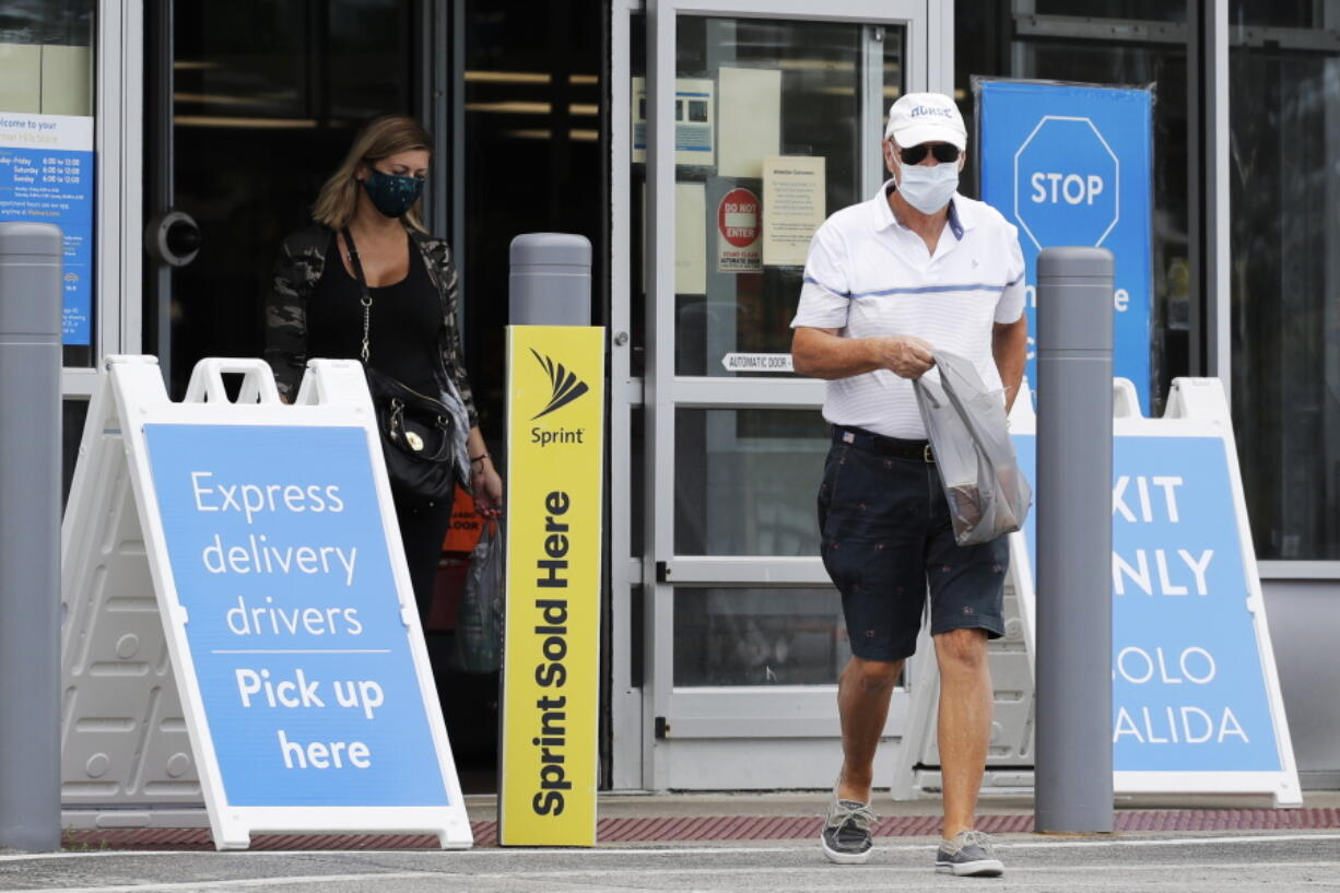 FILE - In this July 30, 2020 file photo, shoppers wear face masks as they leave a Walmart store in Vernon Hills, Ill.  Walmart is reversing its mask policy, Friday, July 30, 2021, and will require vaccinated workers in its distribution centers and stores in areas to wear masks in areas with high infection rates of the virus.  (AP Photo/Nam Y.
