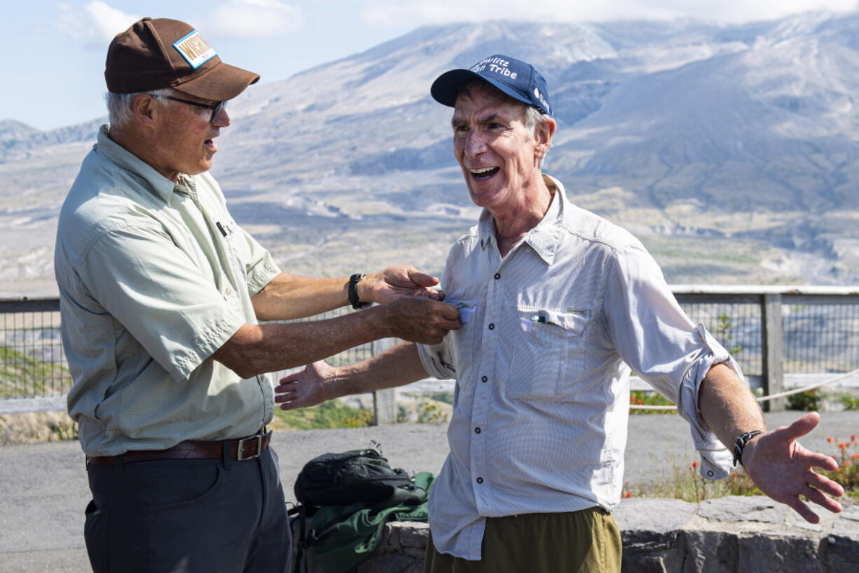 """Gov. Jay Inslee, left, attaches a """"Washingtonian"""" pin to and Bill Nye's shirt during a visit to Johnston Ridge Observatory Thursday."""