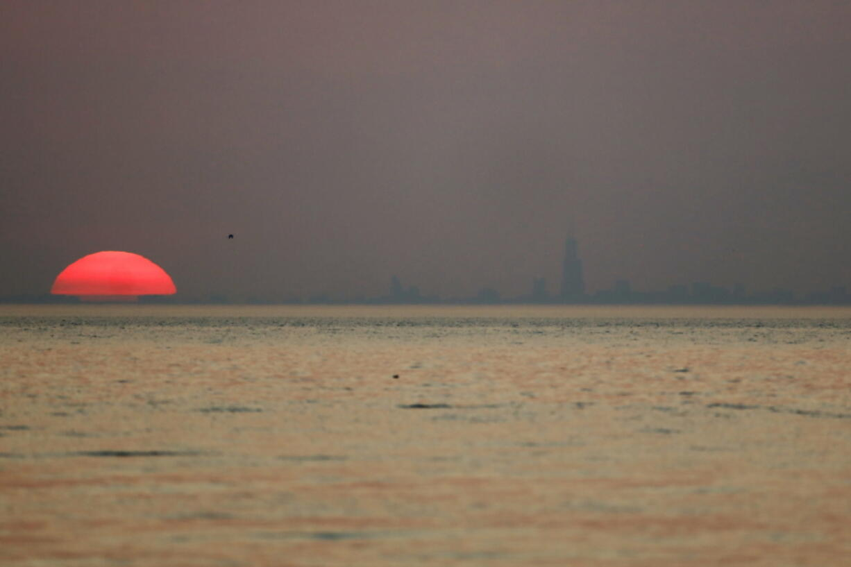 As the sun sets, the Chicago skyline appears through haze emitted from the American West, Tuesday, July 27, 2021, in Indiana Dunes State Park, in Indiana. Wildfires in the American West, including one burning in Oregon that's currently the largest in the U.S., are creating hazy skies as far away as New York.