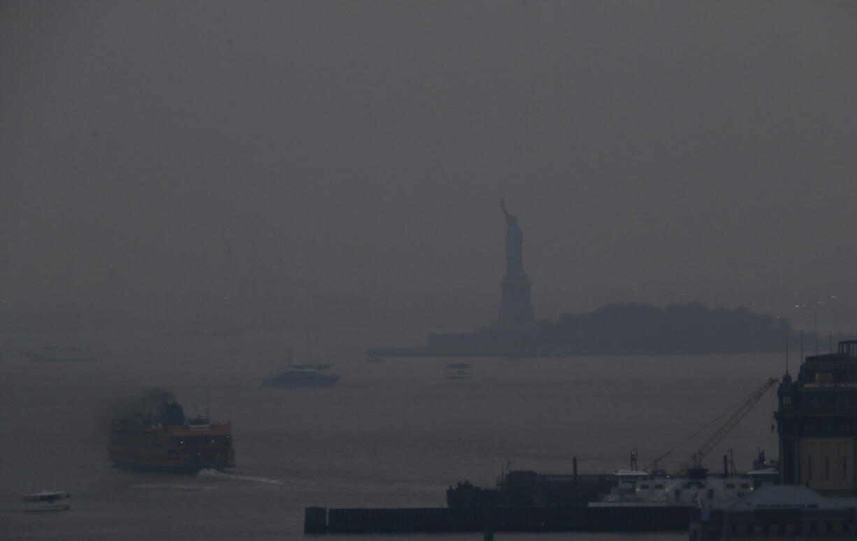The Staten Island Ferry departs from the Manhattan terminal through a haze of smoke with the Statue of Liberty barely visible, Tuesday, July 20, 2021, in New York. Wildfires in the American West, including one burning in Oregon that's currently the largest in the U.S., are creating hazy skies as far away as New York as the massive infernos spew smoke and ash into the air in columns up to six miles high.