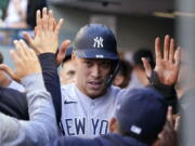 New York Yankees' Aaron Judge is congratulated after scoring against the Seattle Mariners during the first inning of a baseball game Wednesday, July 7, 2021, in Seattle.